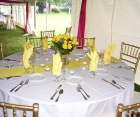 Table set up with dining wear and chiavari chairs inside tent