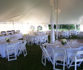 Tent setup with buffet, tables, folding chairs and dance floor